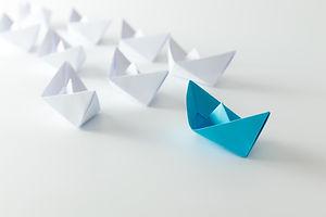 Leadership concept using blue paper ship
