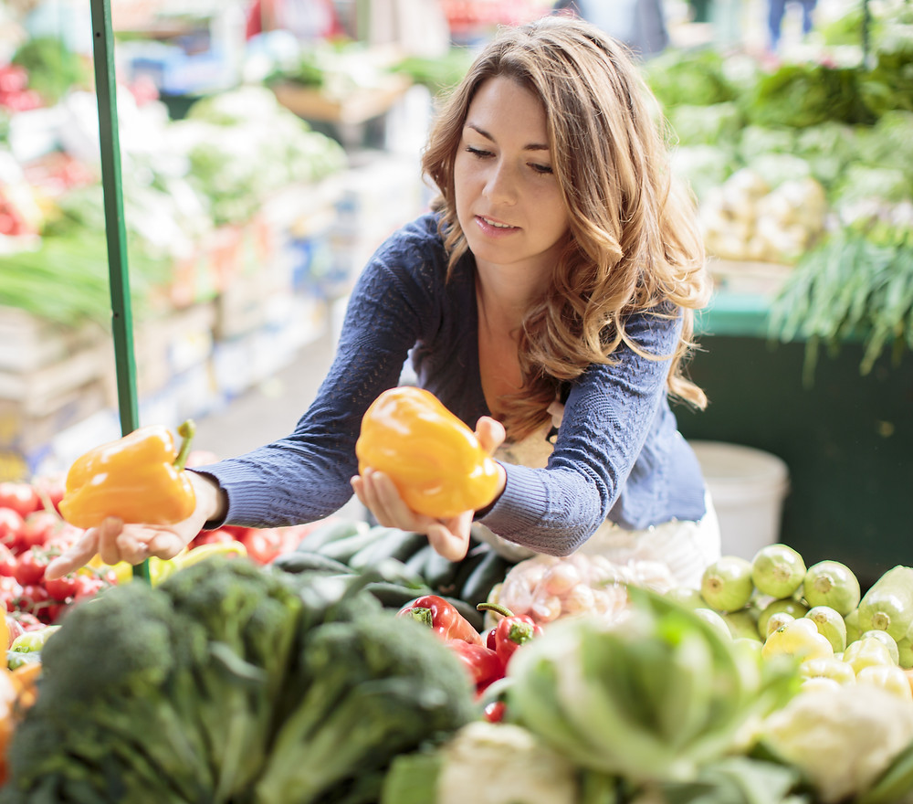 a woman picking out healthy food from a market