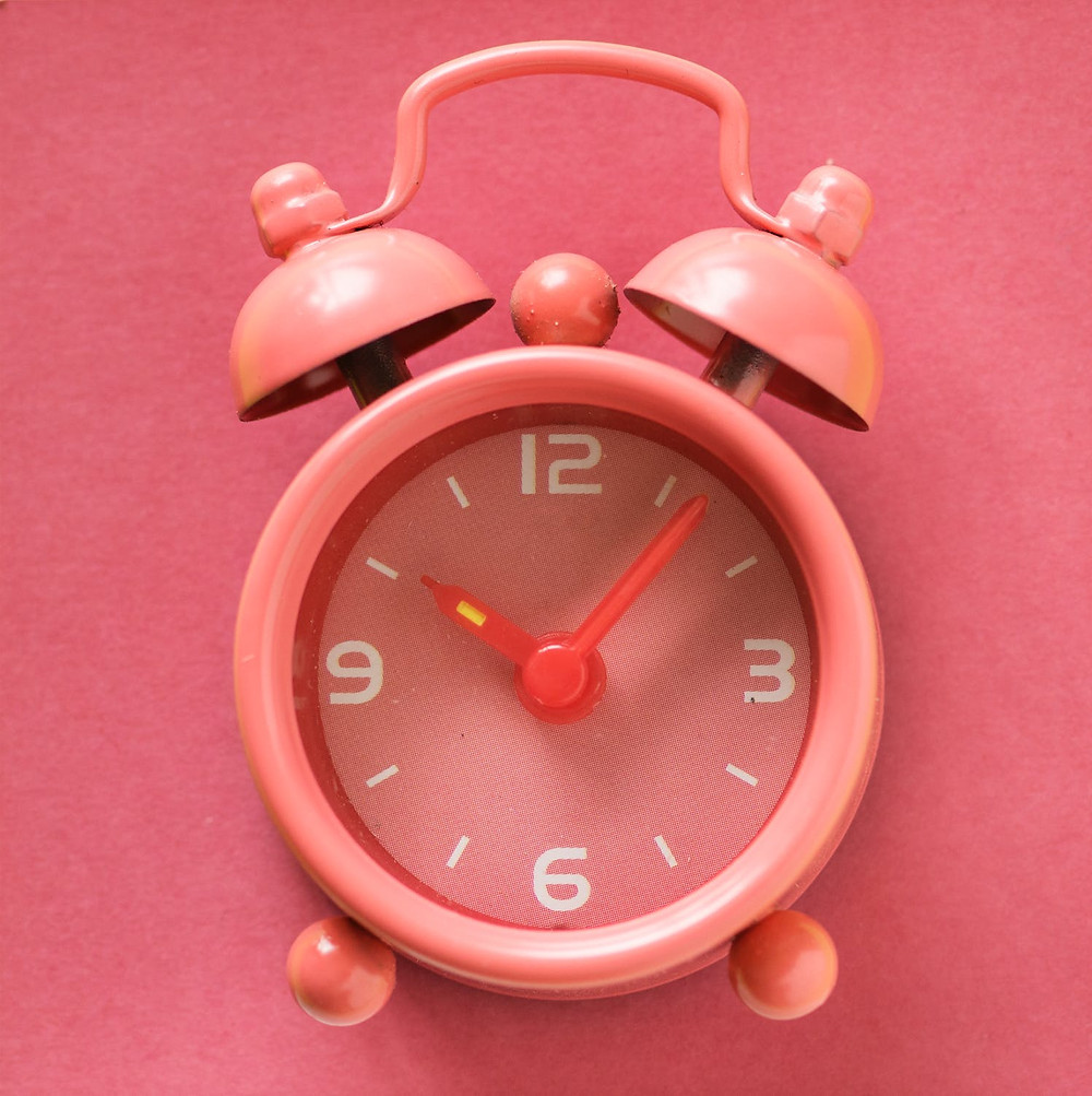 Social media tips with pink alarm clock showing time.