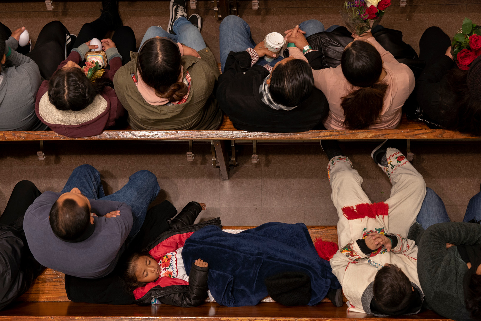 A young girl falls asleep during the 10pm mass at Our Queen Lady of Angeles Catholic Church in Los Angeles, CA.  Every year on December 12th, the Mexican Catholic community commemorates the appearance of Mary to the Mexican peasant Juan Diego in 1531.
