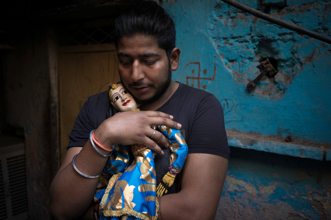 A young man in the Kathputli Colony in New Delhi, India hugs his puppet.  These people are being forced out of their homes so that expensive highrises can be built.  The people of the colony who come from generations of magicians, snake charmers, puppeteers, and artists have lived in this community since the 1950's.