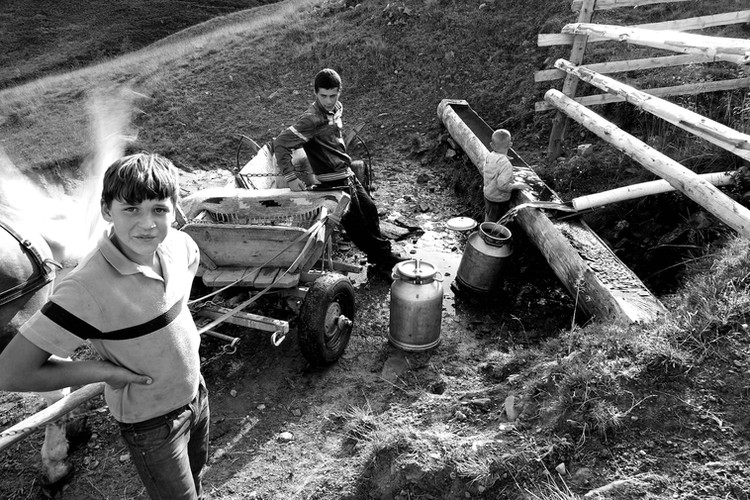 Ukranian boys in the Carpathian Mountains gather fresh water for the day.  During the summer months, people will travel higher into the mountains to make cheese to sell while it's in season.