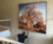 A wall art print of a baobab tree is being installed in a modern home.