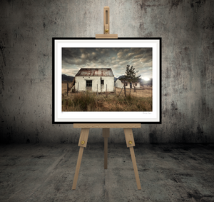 A picture of two old farm sheds in frame on an easel.