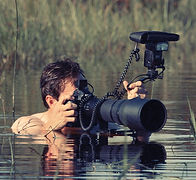 Greg Du Toit WIldlife Photographer in a waterhole photographing animals