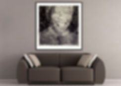 A black and white portrait of Nelson Mandela displayed on a wall in a black frame above a couch.