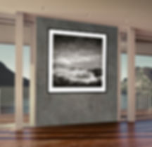 Black and white seascape print in a black frame shown in a modern interior
