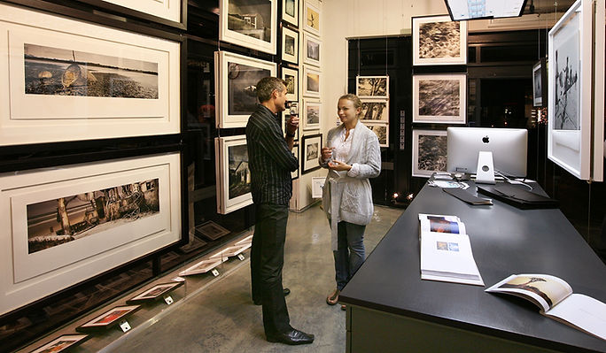 Inside of a modern photography gallery where beautiful prints are displayed in large frames.