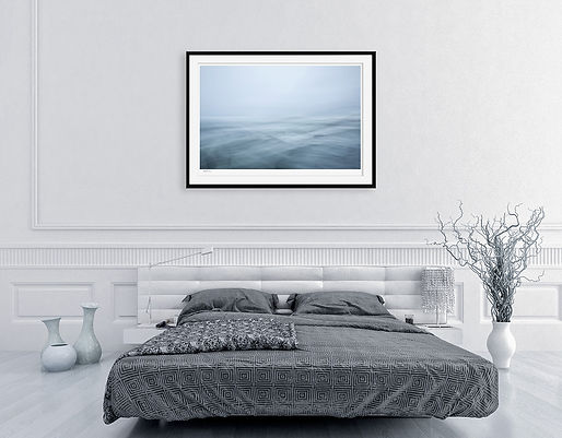 A calming blue abstract photograph of the ocean is displayed in a frame as wall art in a modern bedroom.
