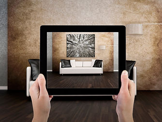 A woman holds an iPad up to see what a photograph will look like as wall art.