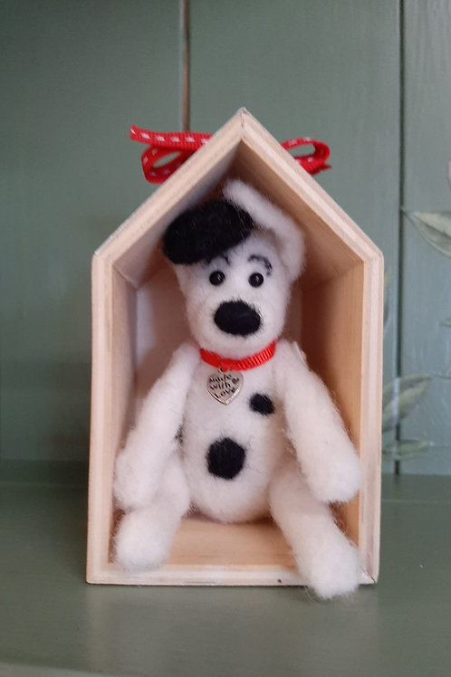 Jointed felt puppy in a kennel