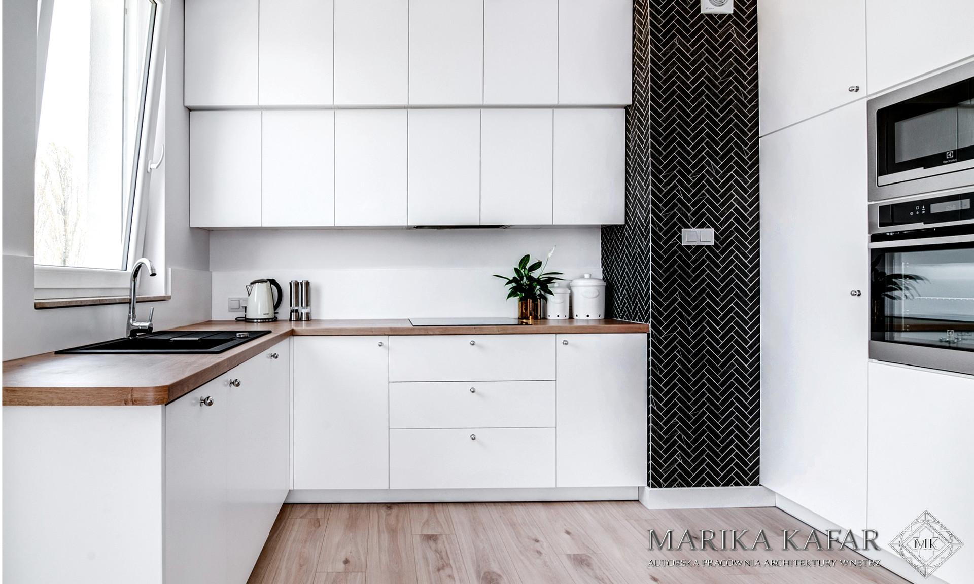 Marika Kafar. Biała kuchnia z drewnianym blatem i czzarną jodełką.