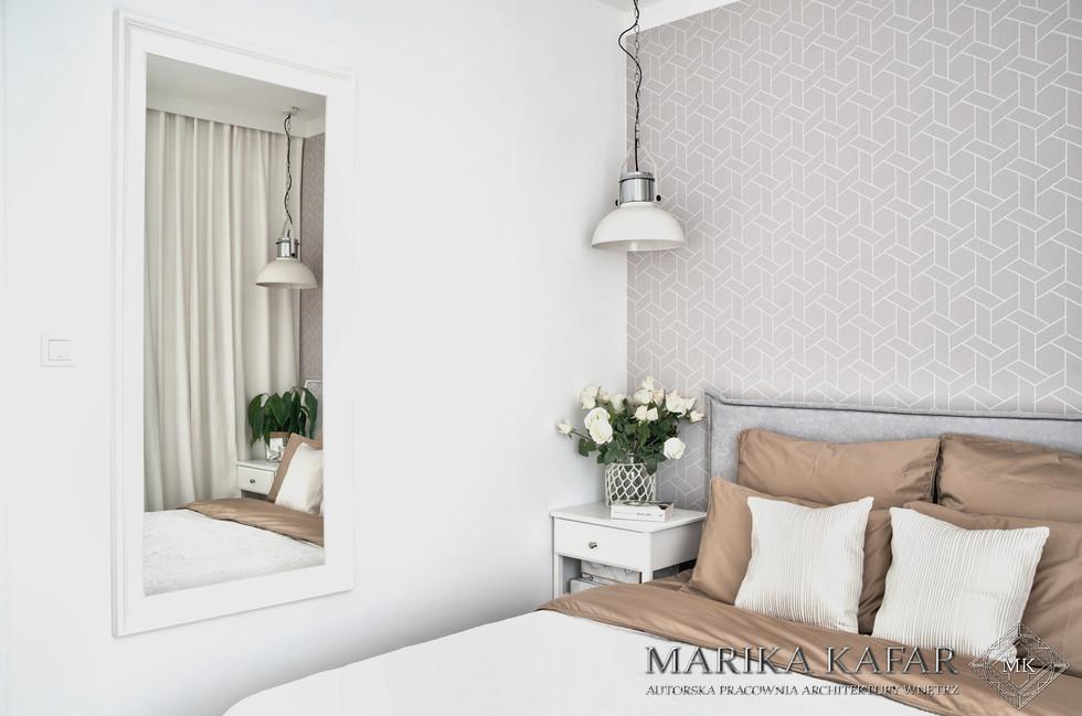 Marika Kafar. Projekt sypialni z delikatną, wzorzystą tapetą nad łóżkiem.