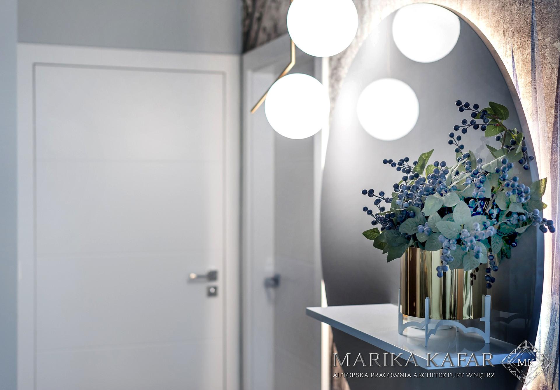Marika Kafar . Designerska lampa w otoczeniu wzorzystej tapety.