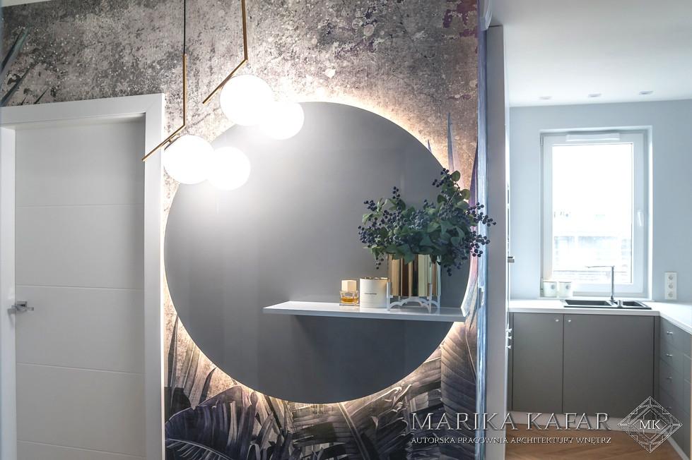 Marika Kafar. Projekt holu z charakterystycznym, dużym, podświetlonym lustrem i tapetą w ornamentalne wzory.