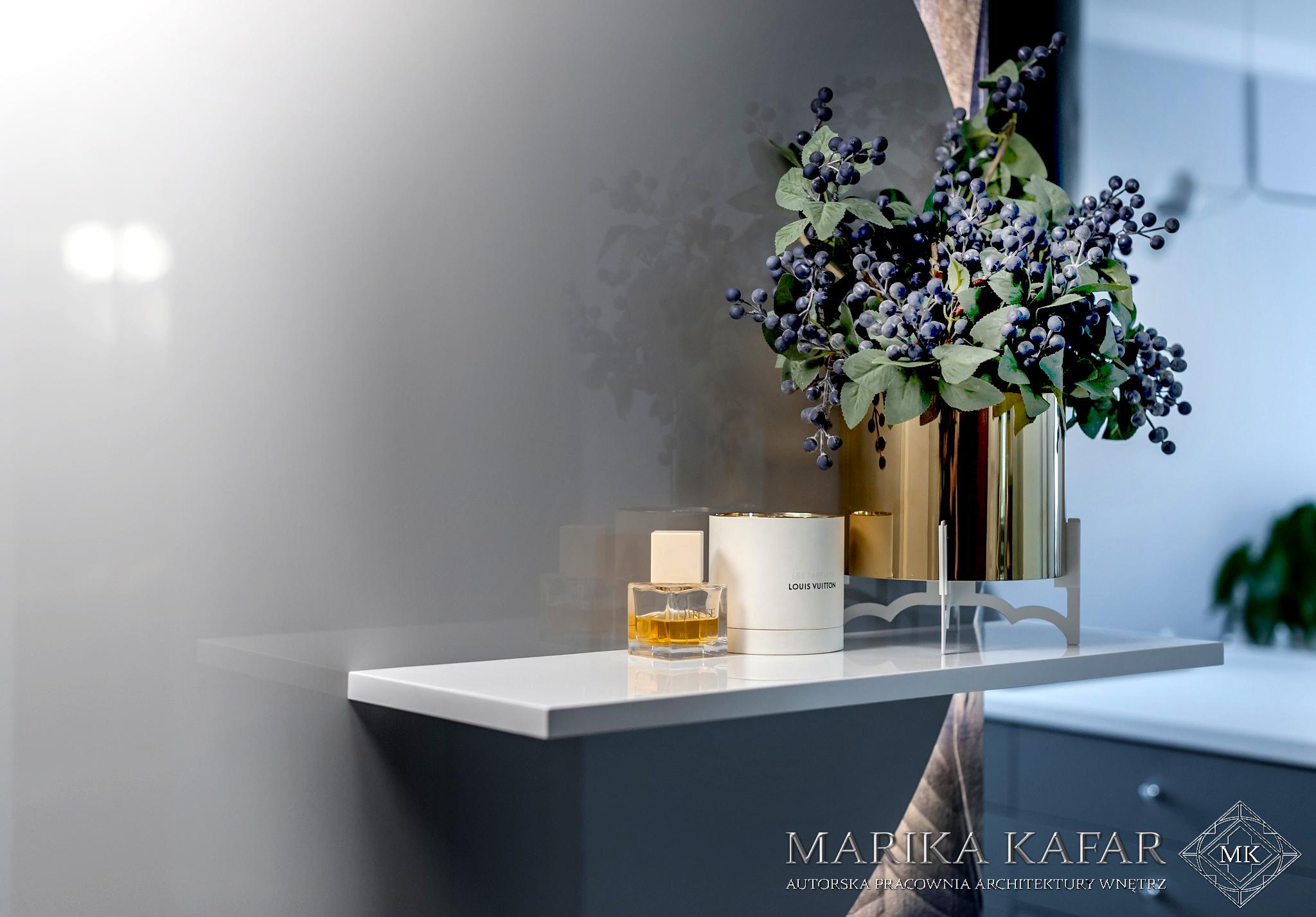 Marika Kafar. Wnętrze z dużą ilością kwiatów.