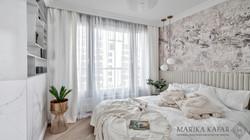 Marika Kafar. Jasna subtelna sypialnia z tapetą nad łóżkiem.