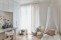 Marika Kafar.Przytulny pokój dziecięcy w jasnej kolorystyce, z elementami różu i złota.
