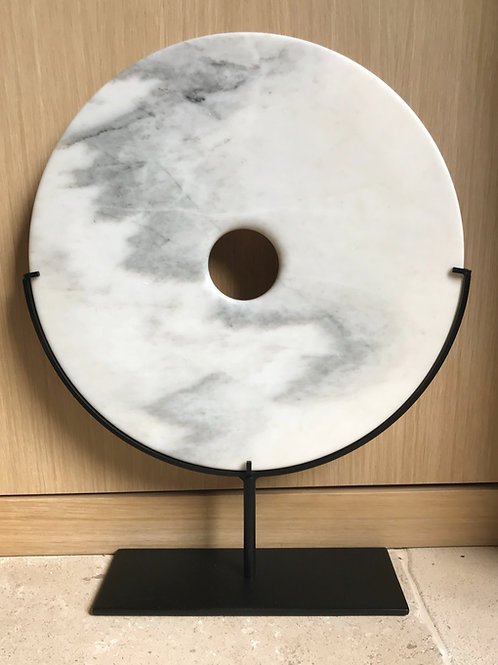 White marble disc artifact on stand