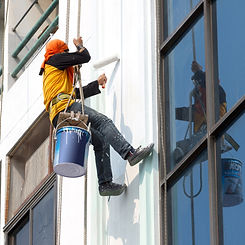 Painter hanging on the outside of a building to paint the exterior wall with a roller and white paint.
