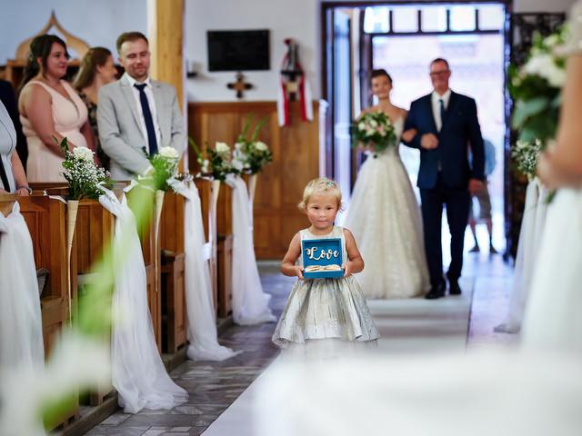 dziecko niesie obrączki pary młodej
