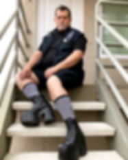 Peter Ambrose, master stylist, sitting on the stairs in chunky high heeled boots and striped socks