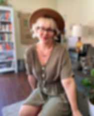 Raeanne Deady, stylist, sitting in living room in a tan dress with big hat