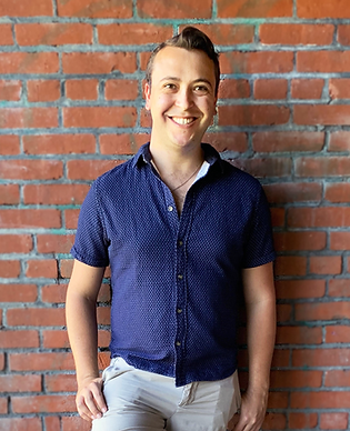 Tyler Flood, stylist standing in front of a brick wall in a blue shirt