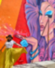 Louise (Weezy) Health-Kolb in yellow skirt standing in front of drag queen mural