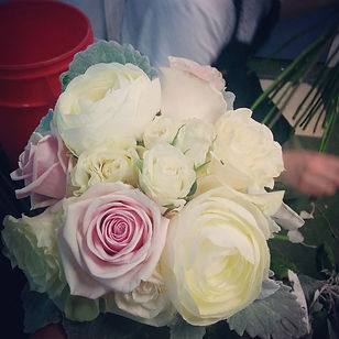 handtied bridesmaids bouquet with blush roses white roses and white ranunculus and dusty miller accents