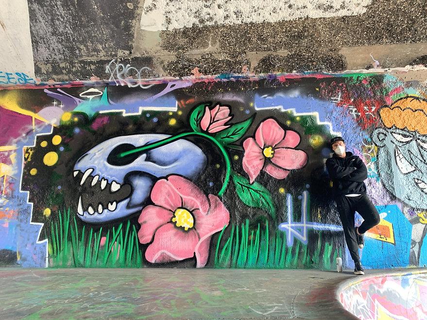 josh harnack standing by his mural at leeside skatepark