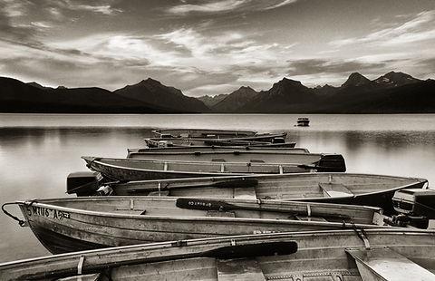 Boats on Lake McDonald Montana black and white photograph by Scott Wheeler