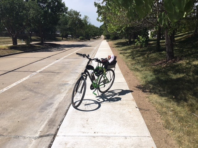 Dale Kling's Green Bike on an unfinished sidewalk