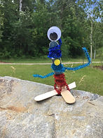 A blue and red popsicle puppet alien stands propped outside on a rock with trees in the background