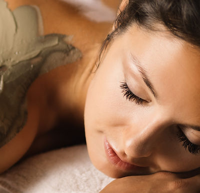 The girl enjoys mud body mask in a spa s