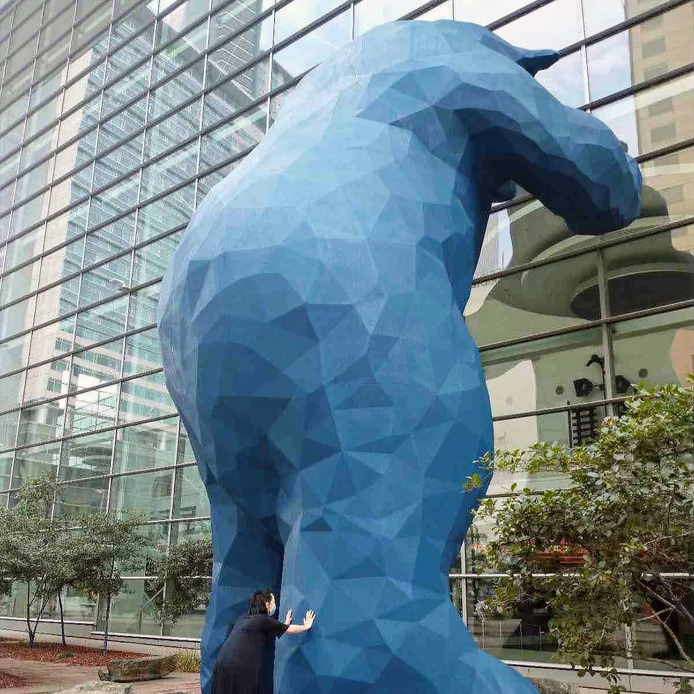 A Colorado School of English student is posing with the big blue bear statue outside the Colorado Convention center in Denver.