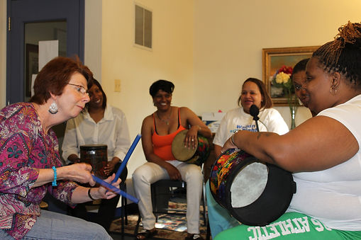 Women playing instruments with Harmony, Hope, & Healing Founder Marge Nykaza leading them in song.