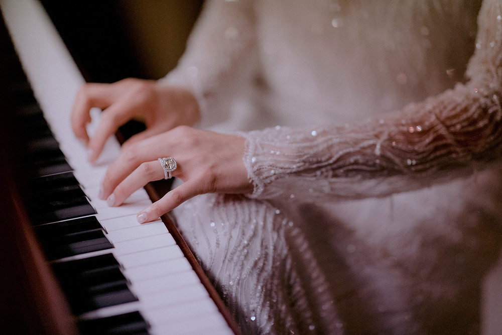 A woman plays the piano with a large yellow diamond wedding ring