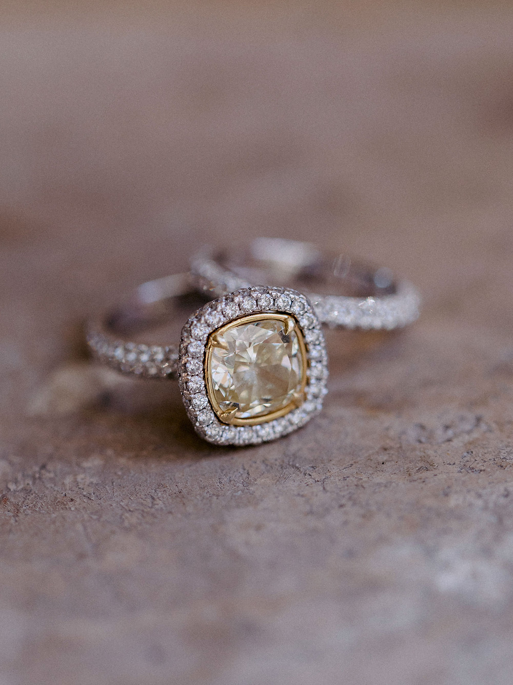 A yellow diamond engagement ring with white diamond halo