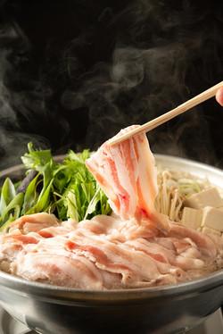 箸で豚肉を持ち上げて黒い背景でシズル感を演出 | 福岡の写真事務所