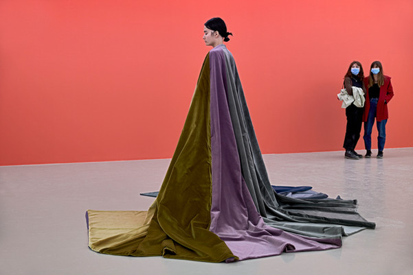 Insulaire (avant l'orage), 2016-2020. Piece for 1 person 170cm tall. Velvet, cotton. 520x520cm. With the help of Julia Richert Lebon. Célia Marthe - IAC Villeurbanne.  Inspired by the scientific diagrams of the visual field, Insulaire is displayed as a drawing on the floor. It captures the colour of a stormy sky, translated into velvet sections which create shiny and unpredictable effects as we gradually skirt it. If we stand in the middle, we could open our mind to this sketch horizon. Insulaire is also wear as a cape by a still female performer, as she brings the sky on her shoulders.  ©Thomas Lannes
