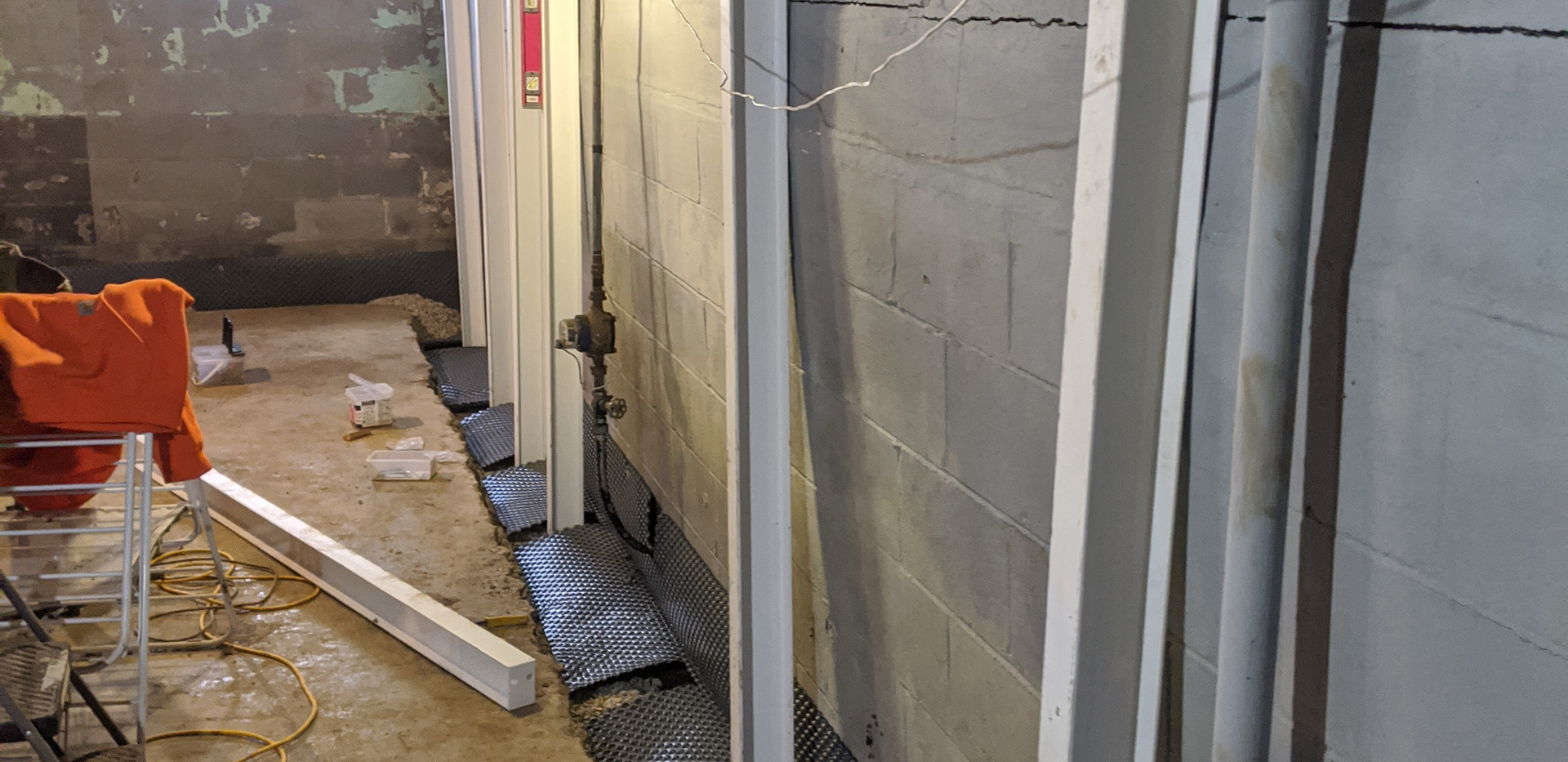 Basement waterproofing with installation of an interior drain tile system