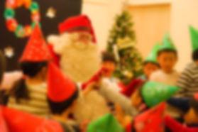赤や緑の帽子を被った子どもたちにサンタさんが囲まれている様子