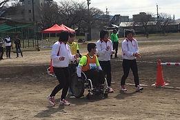 車いすで走るランナーと一緒に伴走する女子プロ野球選手たちの写真
