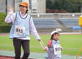 笑顔で走る親子の写真