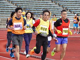 ブラインドラン競技 ブラインドランナーと伴走者がキズナを手に力走する写真