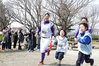 キズナペアランで女子プロ野球選手と一緒に走る子どもの写真
