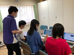 パソコンをお届けし、操作方法を生徒に教える様子