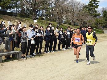 応援する多くの方々の前を疲れた表情で走るランナーの写真