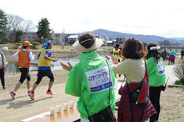 賀茂川河川敷を走るランナーとそのランナーを応援する様子の写真